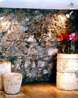 Top of an ancient column engraved with seven menorahs, in front of an exposed wall from 2000 years ago
